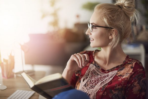 woman in glasses reading on porch