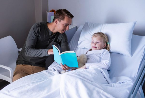 volunteer reading to a sick child