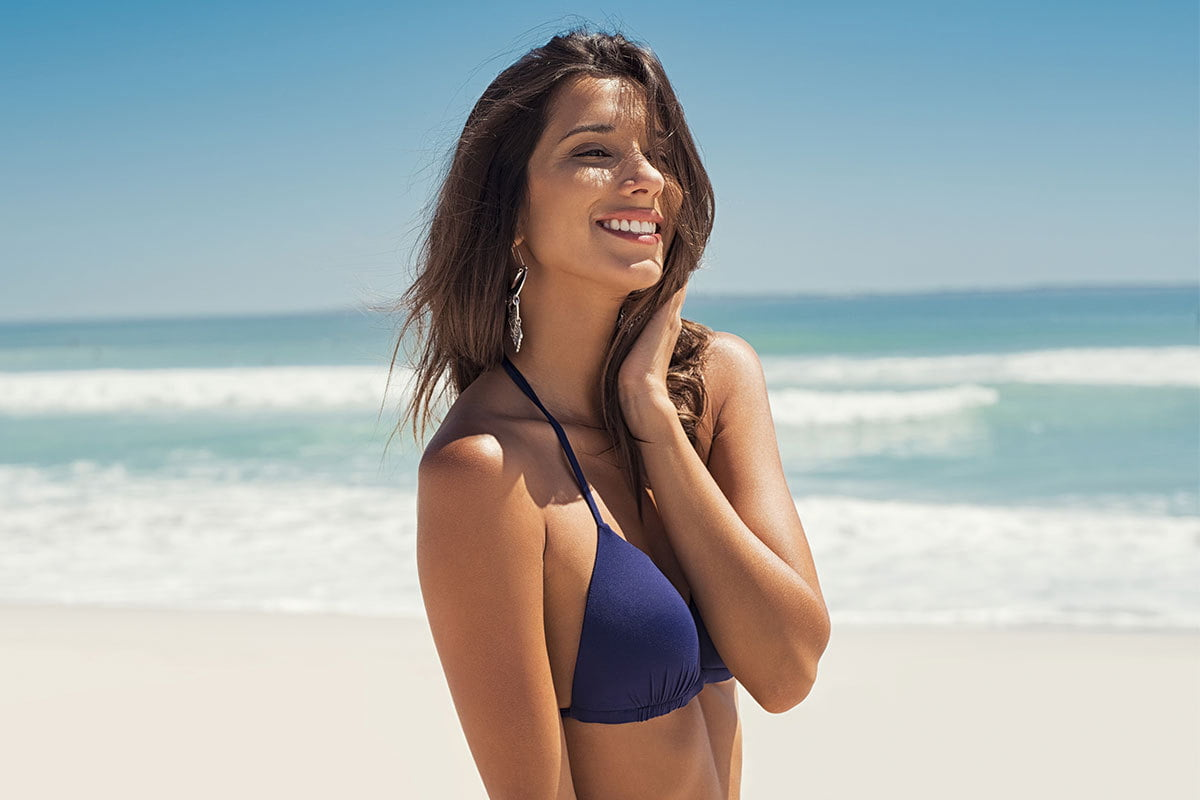 happy woman considering a breast lift asks questions to dr. emily kirby