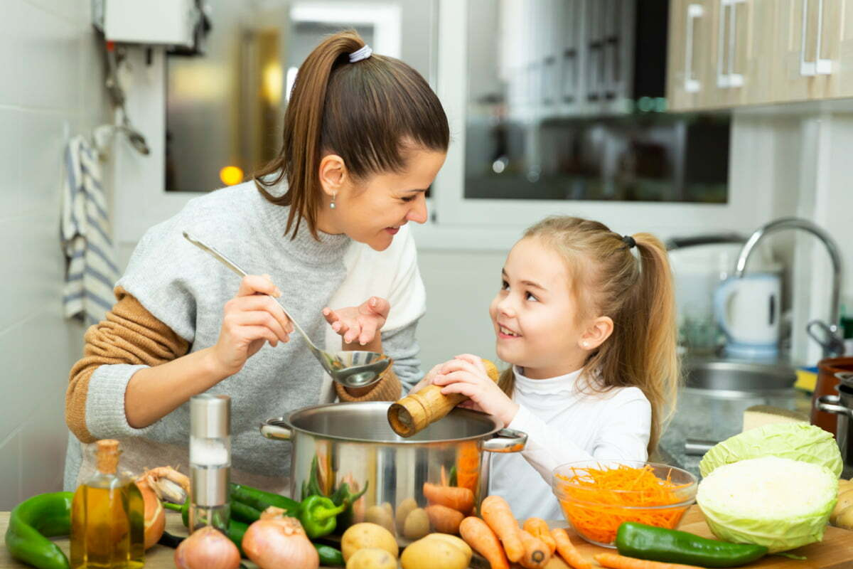 Mother and Daughter Cooking a Healthy Meal Inspired by the New USDA Nutrition Guidelines