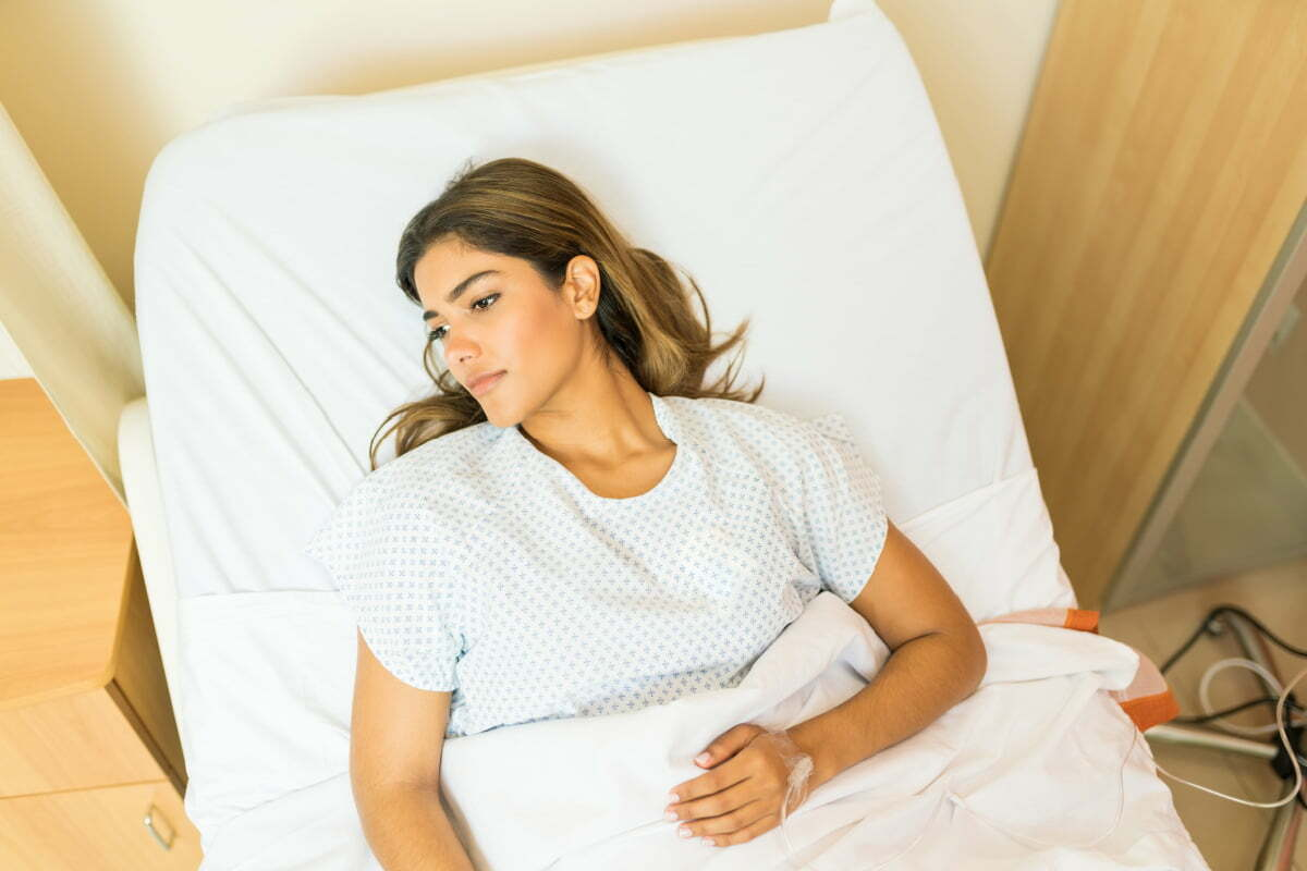 Woman Recovering in Hospital Bed Following Plastic Surgery Procedure
